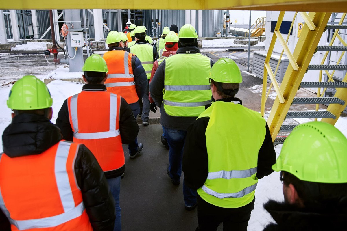 Stakeholders in safety gear walking through workplace
